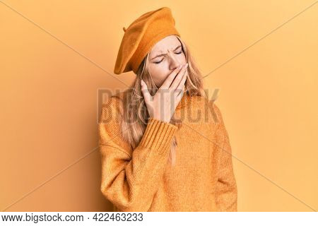Beautiful young caucasian girl wearing french look with beret bored yawning tired covering mouth with hand. restless and sleepiness.