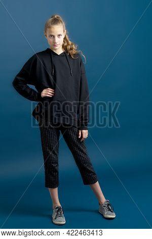 Pretty Teenage Girl In Black Hoodie. Portrait Of Girl Wearing Black Sweatshirt Standing With Hand On