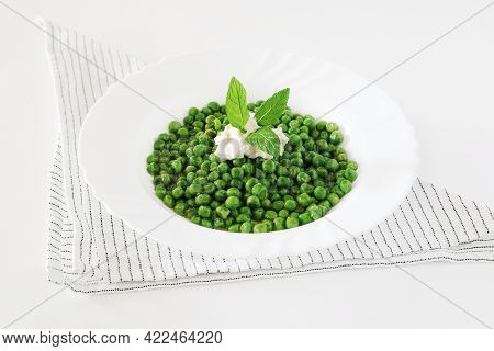 Lemon Peas - Blanched Peas With Cream And Lemon Zest On A White Wooden Table With A Kitchen Towel.