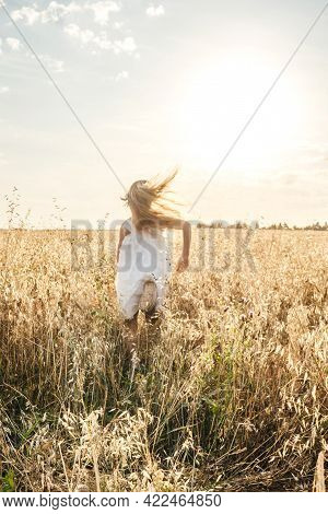 Young Mother And Daughter In Field Blurred. Sun Background, Grass On Foreground In Focus. Love And F