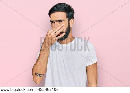 Young hispanic man wearing casual white t shirt smelling something stinky and disgusting, intolerable smell, holding breath with fingers on nose. bad smell