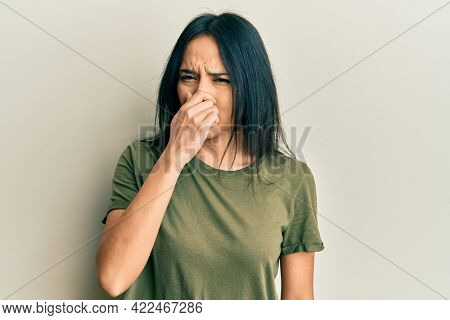 Young hispanic girl wearing casual t shirt smelling something stinky and disgusting, intolerable smell, holding breath with fingers on nose. bad smell