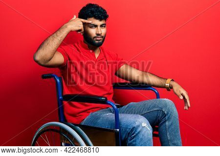 Arab man with beard sitting on wheelchair pointing unhappy to pimple on forehead, ugly infection of blackhead. acne and skin problem