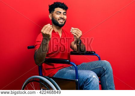 Arab man with beard sitting on wheelchair doing money gesture with hands, asking for salary payment, millionaire business