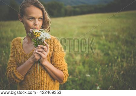 Beautiful young woman outdoors with a bouquet of wild flowers in a field, enjoying nature. Happy Woman on spring meadow