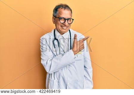 Middle age indian man wearing doctor coat and stethoscope cheerful with a smile of face pointing with hand and finger up to the side with happy and natural expression on face