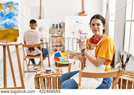 Young artist woman painting on canvas at art studio pointing aside worried and nervous with forefinger, concerned and surprised expression