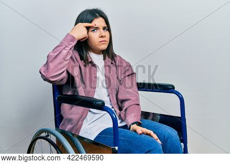 Young brunette woman sitting on wheelchair pointing unhappy to pimple on forehead, ugly infection of blackhead. acne and skin problem