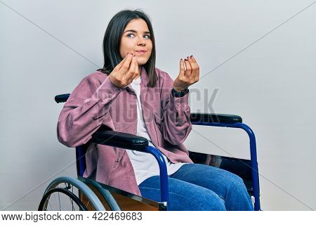 Young brunette woman sitting on wheelchair doing money gesture with hands, asking for salary payment, millionaire business