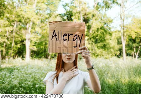 Young Redhead Woman Covers Her Face With Sign Text Allergy. Faceless Portrait Of Woman Holding Aller