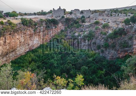 Panoramic View Onto Ruins Of Buildings, Standing Near Edge Of Karst Sinkhole In Ancient City Kanli D
