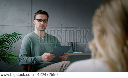 A young professional psychotherapist conducts an interview with a patient in the office