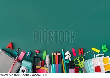 Office Stationery With Medical Mask And Headphones On Green Background