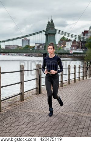 Beautiful Young Slim Woman Is Jogging Along The Embankment Of The River In London. Stay Healthy, Do