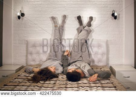A Young Heterosexual Couple Is Lying On The Bed With Their Legs Up Against The Wall And Holding Each