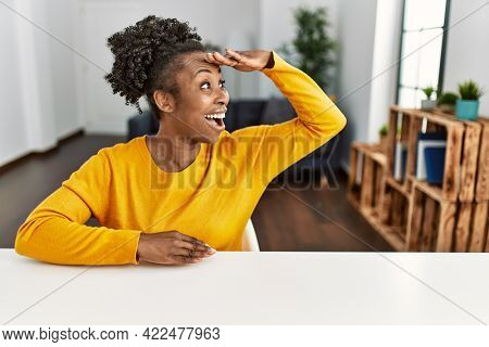 Young african american woman wearing casual clothes sitting on the table at home very happy and smiling looking far away with hand over head. searching concept.