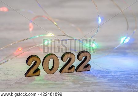 Wooden Figures 2022 And Garland. Banner 2022. Figures 2022 On Beige Background. New Year's Calendar.