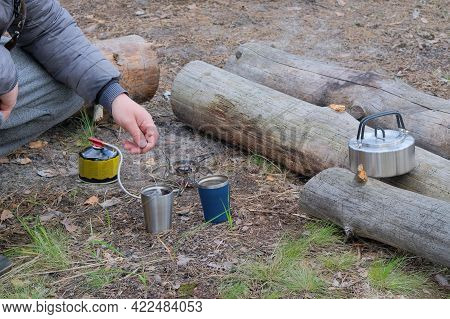 Tourist Food For Outdoor Activities. Traveler Is Making Tea In A Mug During Camping. Enjoy A Tasty F