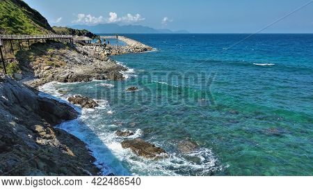 A Pedestrian Path With A Rope Railing Winds Along The Mountainside, Above The Sea. Turquoise Waves F