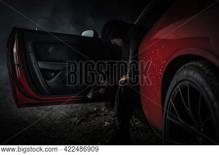 Pensive Caucasian Gangster In His 40s Wearing Black Hoodie With Handgun In His Hand Inside Red Muscl