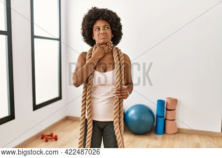 Young african american woman with afro hair at the gym training with battle ropes touching painful neck, sore throat for flu, clod and infection