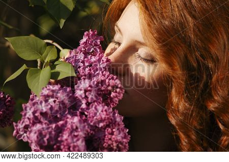 A Beautiful Young Woman With Red Curly Hair And Freckels In A Purple Dress Inhales The Scent Of The