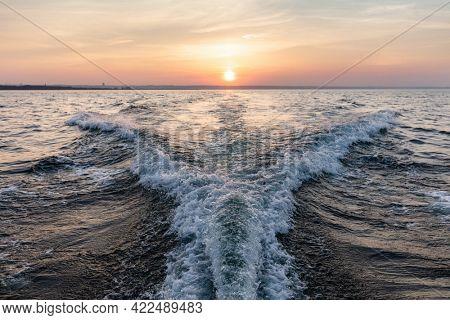 Motorboat wake pattern on sea at sunset.