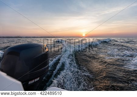 Fast motorboat ride on sea at sunset. Wake pattern behind