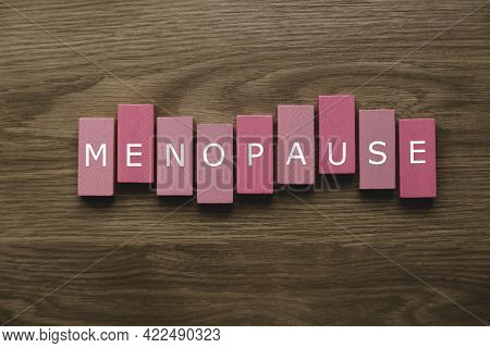 A Pink Wooden Block With A Text Of Menopause On Wooden Background.