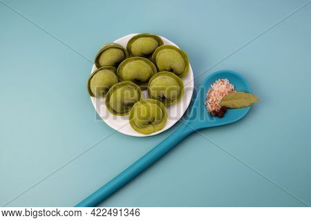 Green Frozen Dumplings In A Round Plate And A Blue Spoon With Spices. Homemade Frozen Dumplings On A