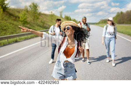 Young Caucasian Woman With Her Multiracial Friends Hitchhiking On Highway, Traveling By Autostop, Ou