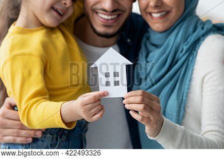 New Home. Happy Muslim Family Holding Cutout Paper House Figure In Hands