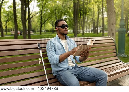 Young Black Visually Impaired Man Sitting On Bench In City Park, Reading Braille Book Outdoors
