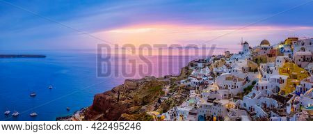 Famous greek iconic selfie spot tourist destination Oia village with traditional white houses and windmills in Santorini island on sunset in twilight, Greece