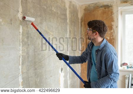 Caucasian Man Painting Cement Walls Using Roller Brush And Primer Making A Renovation.