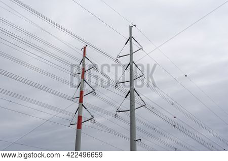 A Close Up View Of Tall Lattice Crosses And High Voltage Power Lines Under An Overcast Sky