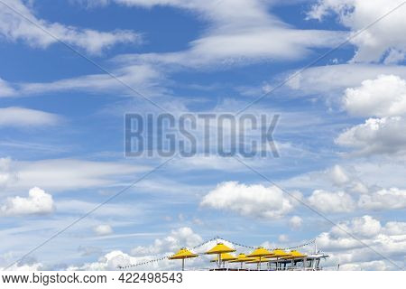 Open Yellow Parasols At An Cruise Ship With Spectacular Blue And Soft Cloudy Sky As Symbol For Touri