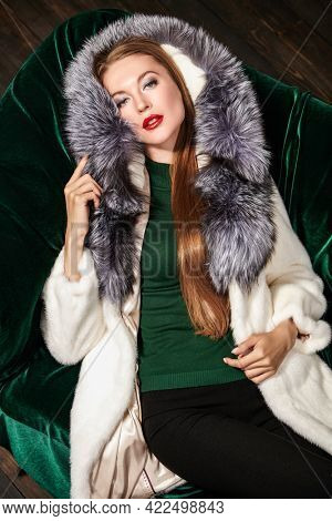 Fur coat fashion. Gorgeous blonde woman in an expensive mink and silver fox fur coat posing on a sofa. Fashion shot. Luxury lifestyle.