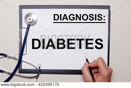 On A Light Background, A Stethoscope And A Sheet Of Paper, On Which A Man Writes Diabetes. Medical C