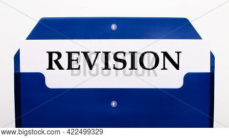 On A White Background, A Blue Folder For Papers. In The Folder Is A Sheet Of Paper With The Word Rev