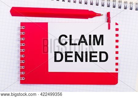 On A White Notepad, A Red Pen, A Red Notepad And A White Sheet Of Paper With The Text Claim Denied