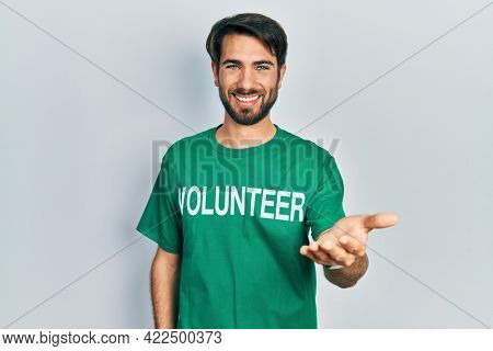 Young hispanic man wearing volunteer t shirt smiling cheerful offering palm hand giving assistance and acceptance.