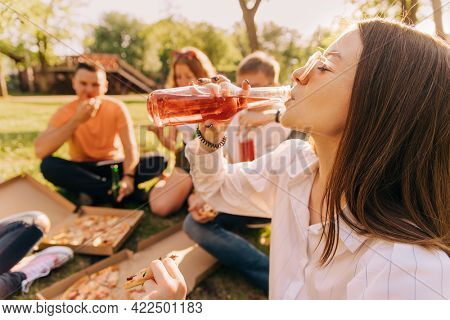 Young girl drinking alcohol and eating pizza with her friends outdoors.