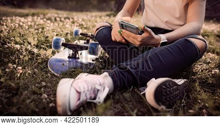 girl skateboarder sitting on a board and using a smartphone, close-up.