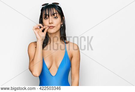 Young hispanic woman wearing swimsuit and sunglasses mouth and lips shut as zip with fingers. secret and silent, taboo talking