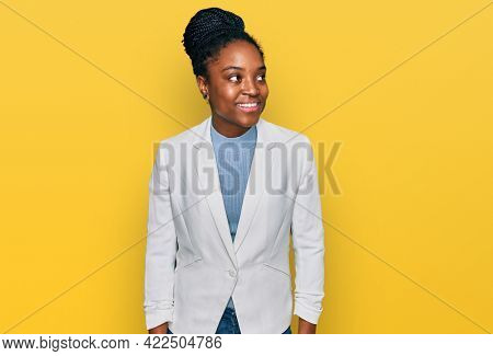 Young african american woman wearing business clothes smiling looking to the side and staring away thinking.
