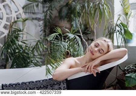 Body Care, Spa And Natural Beauty Concept. Young Dreamy Woman Resting In Bathroom, Lying In Bath At
