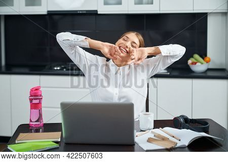 Attractive Woman Stretching Body While Sitting At Kitchen Table During Remote Work On Laptop. Overwo
