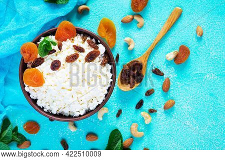 Healthy Breakfast Cottage Cheese With Raisins, Dried Apricots, Almond, Cashew And Mint. Top View