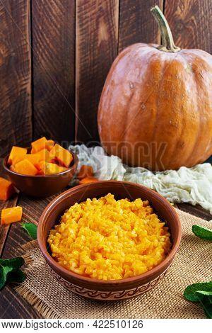 Delicious Homemade Pumpkin Porridge On Wooden Background. Healthy Vegan Food